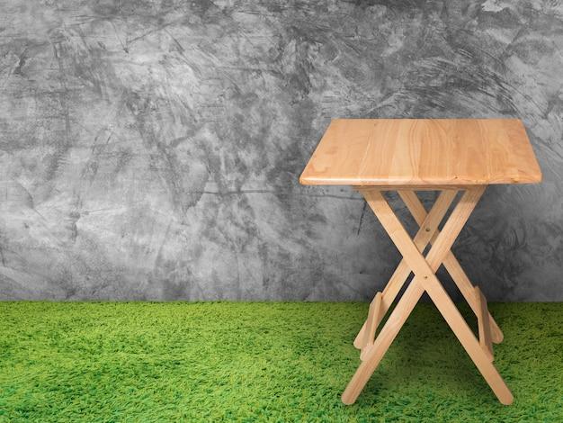 Mesa de madeira com parede de cimento e grama verde