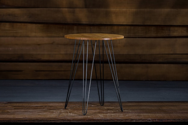 Mesa de madeira com pés de metal e parede de madeira