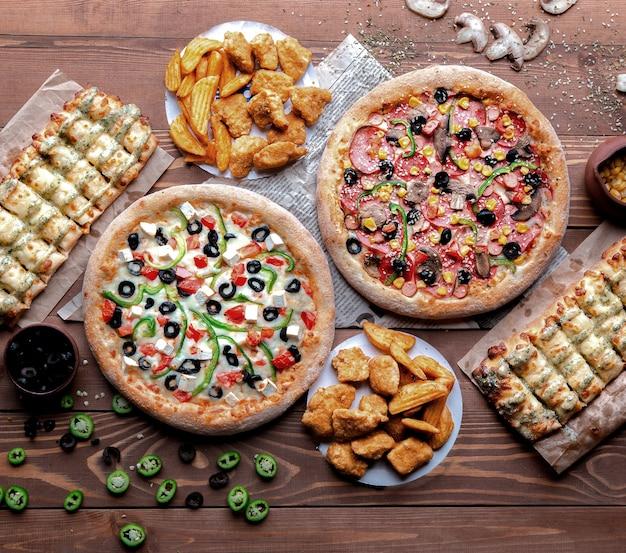 Mesa de madeira com pizzas e lanches nele