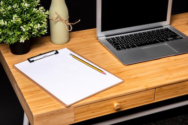 Mesa de madeira com prancheta e laptop