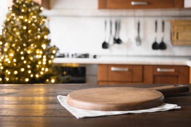 Mesa de madeira com tábua e cozinha moderna turva com árvore de natal.