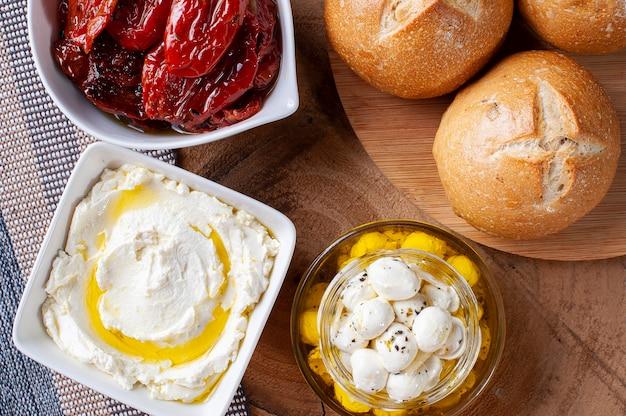 Mesa de madeira com tipos de coalhada e tomate seco para acompanhar o pão