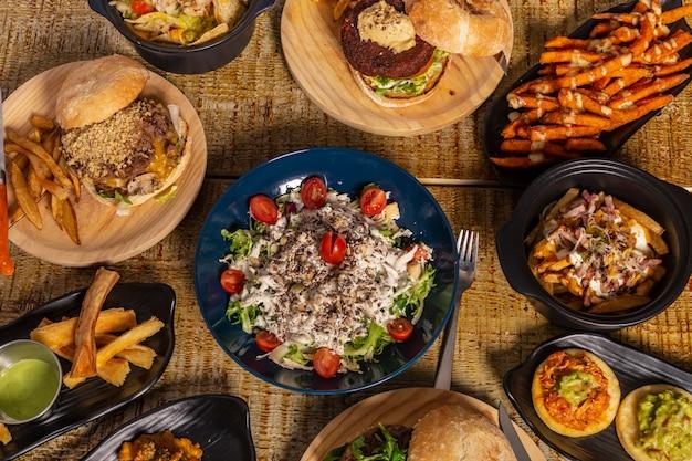 Mesa de madeira com vários pratos de comida mexicana. nachos, hambúrgueres, mandioca frita e batata-doce.