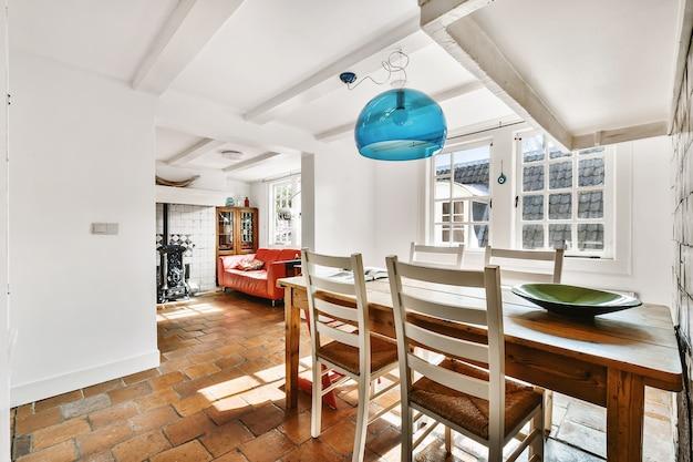 Mesa de madeira com vaso e cadeiras na sala de jantar leve em casa