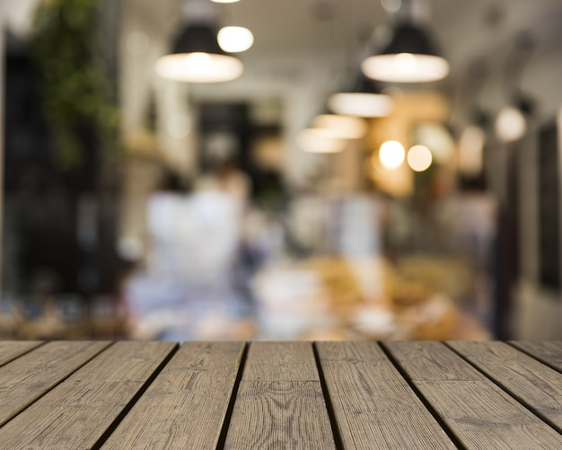 Mesa de madeira com vista para a cena do restaurante embaçada