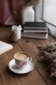 Mesa de madeira com xícara de café e livro
