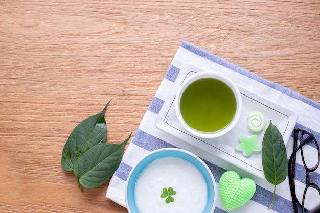 Mesa de madeira da cozinha com o copo do chá verde do matcha e do iogurte orgânico.