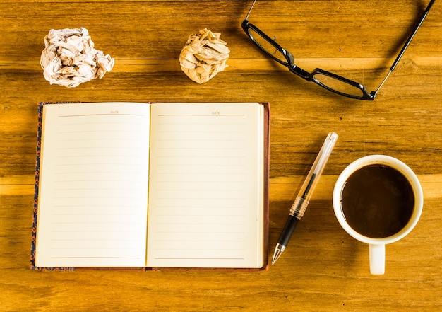 Mesa de madeira de escritório. , notepad, lupa, óculos, caneta e vista do café de cima