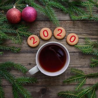 Mesa de madeira de natal com caneca de chá, biscoitos para 2020 ano novo