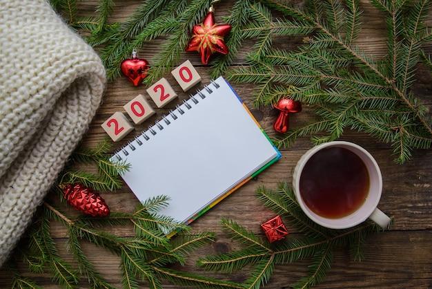 Mesa de madeira de natal com chá, bloco de notas, cachecol, brinquedos para 2020 ano novo
