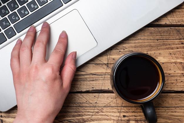 Mesa de madeira de trabalho em casa ou no escritório. cacto de café computador portátil. conceitos de postura plana mulher que trabalha nas mãos do computador.