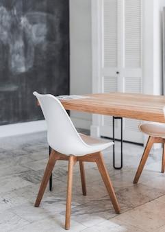 Mesa de madeira e cadeira branca em piso de mármore