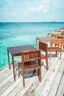 Mesa de madeira e cadeira com vista mar fundo nas maldivas