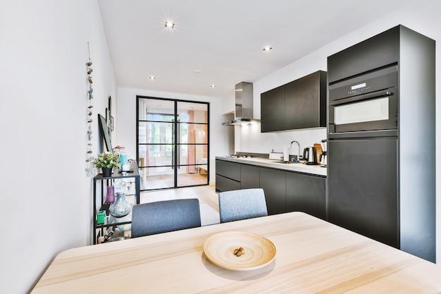 Mesa de madeira e cadeiras confortáveis colocadas perto dos móveis da cozinha em um apartamento moderno e luminoso