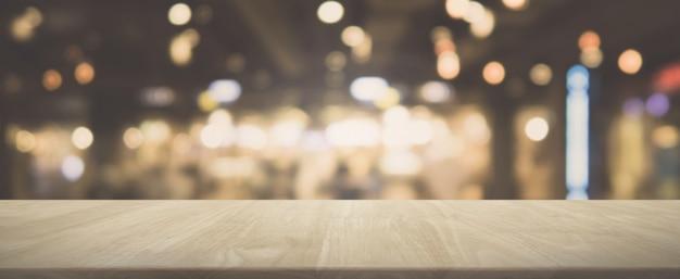 Mesa de madeira e café bokeh borrado e fundo de banner de restaurante com filtro vintage - pode ser usado para exibir ou montar seus produtos.