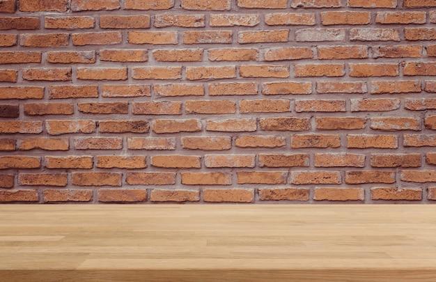 Mesa de madeira e fundo da parede de tijolos velha - pode ser usada para exibir ou montar seus produtos.