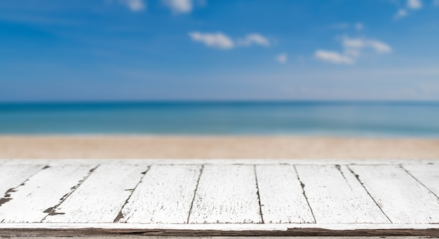 Mesa de madeira e mar azul borrado e fundo do céu. - pode ser usado para exibir ou montar seus produtos.