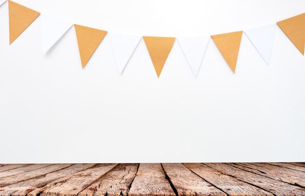 Mesa de madeira e pendurar bandeiras de papel no fundo da parede branca