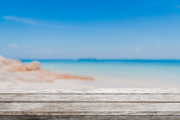 Mesa de madeira e praia de verão borrada com mar azul e céu Foto Premium