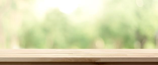 Mesa de madeira em cima de borrão de fundo verde de árvores no parque