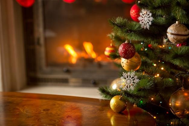 Mesa de madeira em frente a lareira decorada e árvore de natal. lugar para texto. adequado para o fundo de natal.
