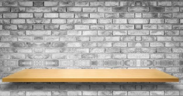 Mesa de madeira em frente à parede de tijolo rústico desfocar o fundo com espaço de cópia vazio na mesa