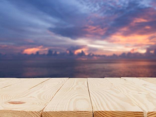 Mesa de madeira em frente à visão borrada abstrata do pôr do sol claro sobre o fundo do mar