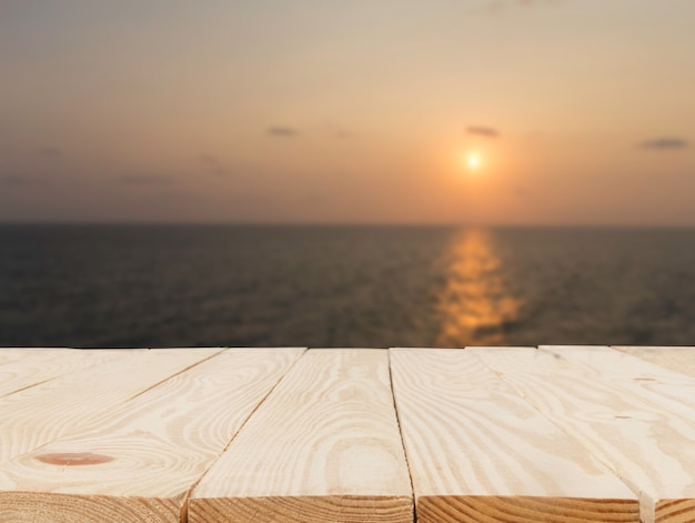Mesa de madeira em frente à visão borrada abstrata do pôr do sol sobre o fundo do mar