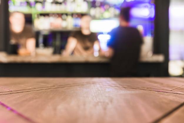 Mesa de madeira em frente ao balcão de bar desfocado