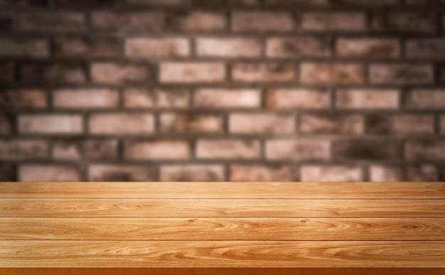 Mesa de madeira em frente ao borrão da parede de tijolo rústico com espaço vazio da cópia na mesa.