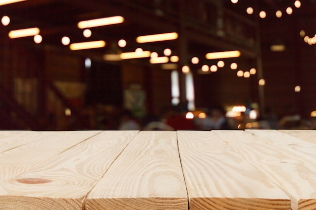 Mesa de madeira em frente ao fundo abstrato bokeh desfocado