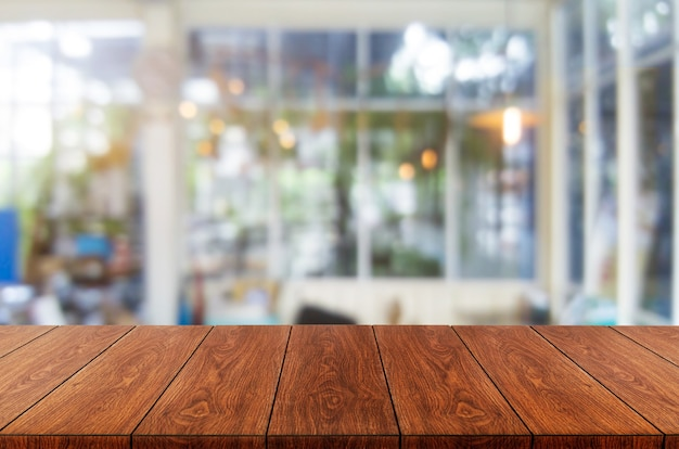 Mesa de madeira em um fundo desfocado da moderna sala de restaurante ou café para maquete de exposição do produto.