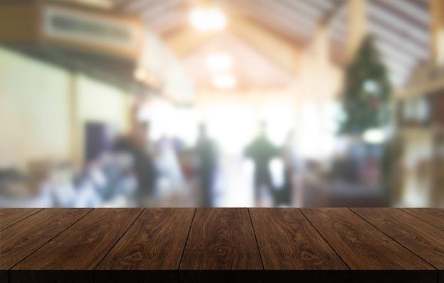 Mesa de madeira em um fundo desfocado de uma moderna sala de restaurante ou cafeteria para exposição de produtos