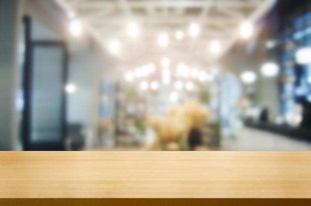 Mesa de madeira embaçada da moderna sala de restaurante ou café para maquete de exposição do produto.