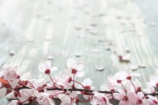 Mesa de madeira envelhecida com um ramo cheio de flores cor de rosa