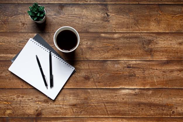 Mesa de madeira escrita, sobre a mesa um caderno e um caderno com uma caneta esferográfica