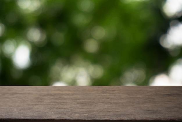 Mesa de madeira escura vazia em frente ao bokeh desfocado abstrato