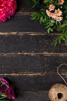 Mesa de madeira escura vintage com flores e barbante