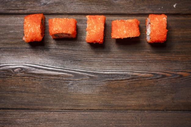 Mesa de madeira gourmet de comida de gengibre vermelho rolls entrega restaurante japonês. foto de alta qualidade