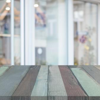 Mesa de madeira listrada na frente da janela de vidro