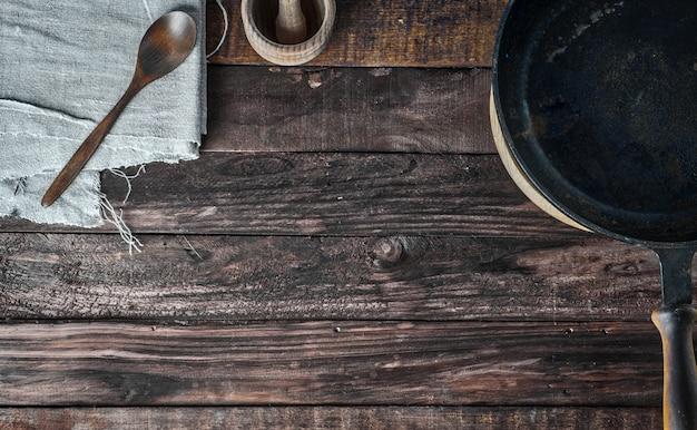 Mesa de madeira marrom com frigideira preta e colher de pau