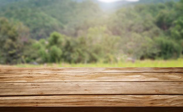 Mesa de madeira marrom em fazenda de verão verde com espaço de cópia vazio na mesa para exposição de produtos