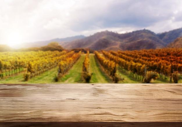 Mesa de madeira marrom em paisagem de vinhedo de outono com espaço vazio para exposição de produtos