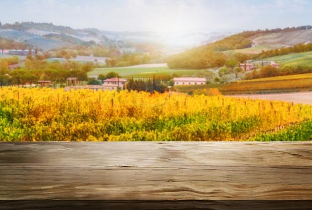 Mesa de madeira marrom na paisagem de vinhedo de outono com espaço vazio para maquete de exposição do produto.