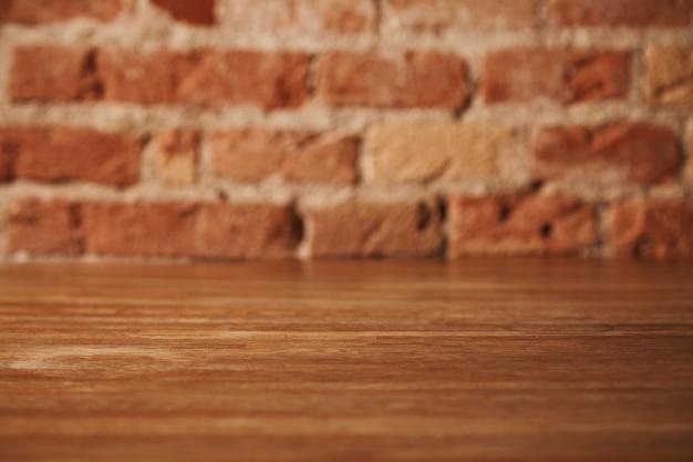 Mesa de madeira marrom rústica vazia com parede de tijolos atrás, fundo para natureza morta e outras composições