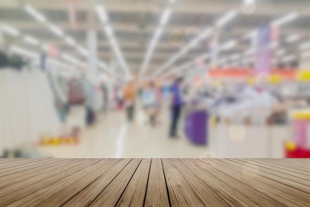Mesa de madeira mesa vazia em frente ao fundo desfocado. perspectiva de madeira clara sobre borrão no supermercado - pode ser usada para exibir ou montar seus produtos. mock up para exibição de produto.