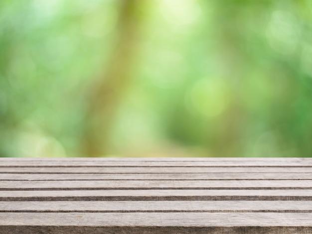 Mesa de madeira mesa vazia em frente ao fundo desfocado. perspectiva madeira marrom sobre árvores desfocadas na floresta - pode ser usado para exibir ou montar seus produtos. temporada de primavera. imagem filtrada vintage.