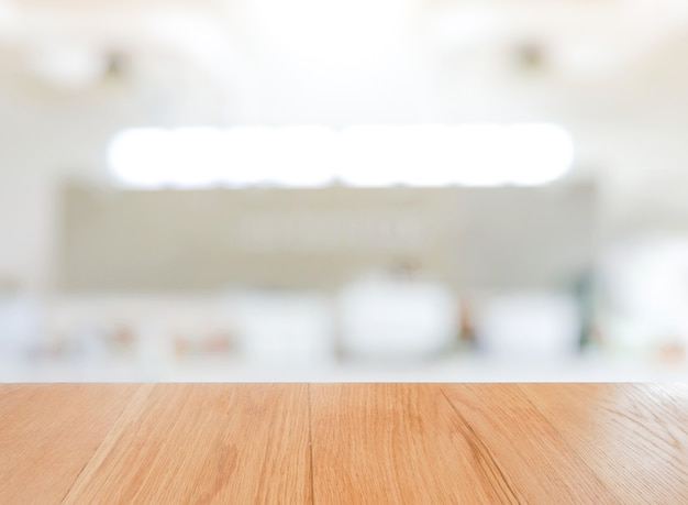 Mesa de madeira mesa vazia na frente do papel de parede branco fundo desfocado no café bar