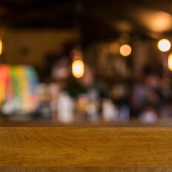 Mesa de madeira na frente das luzes do restaurante turva