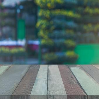 Mesa de madeira na frente do cenário de jardim embaçada